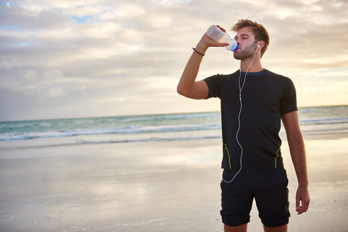 man refreshing with water after a run