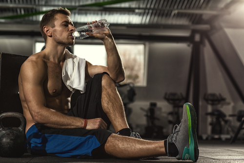 guy drinking water after gym workout