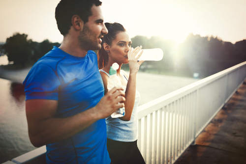 couple drinking water to hydrate after running