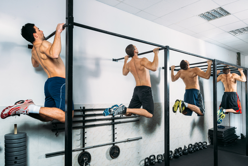 group of fit men doing pull up, chin up