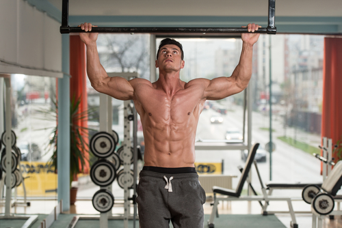 fit muscular man doing pull ups