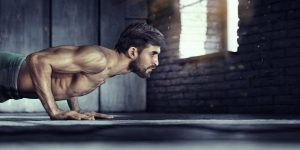 muscular man who takes Progentra regularly doing push ups