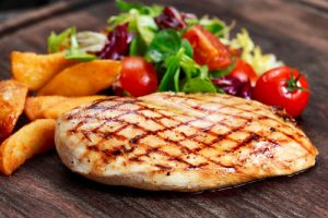 grilled skinless chicken breast with vegetables on side
