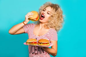woman binge eating hamburgers