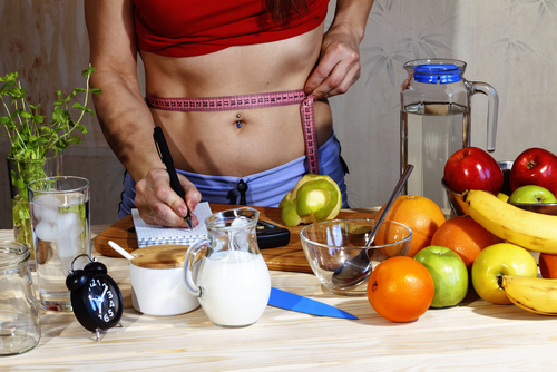 woman measuring waist and writing down, with healthy food on table