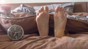 feet of sleeping guy next to alarm clock