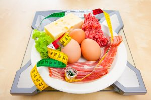low carb diet food on a weighing scale with measuring tape