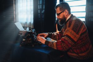 bearded guy typing in an old typewriter