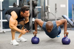 personal trainer coaching a man who uses Progentra doing kettle bell push ups