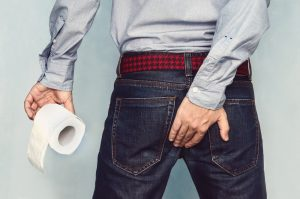 man having diarrhea holding his bum with one hand and toilet paper with the other