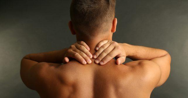 man rubs shoulder and neck