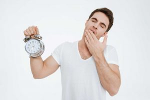 tired man with alarm clock